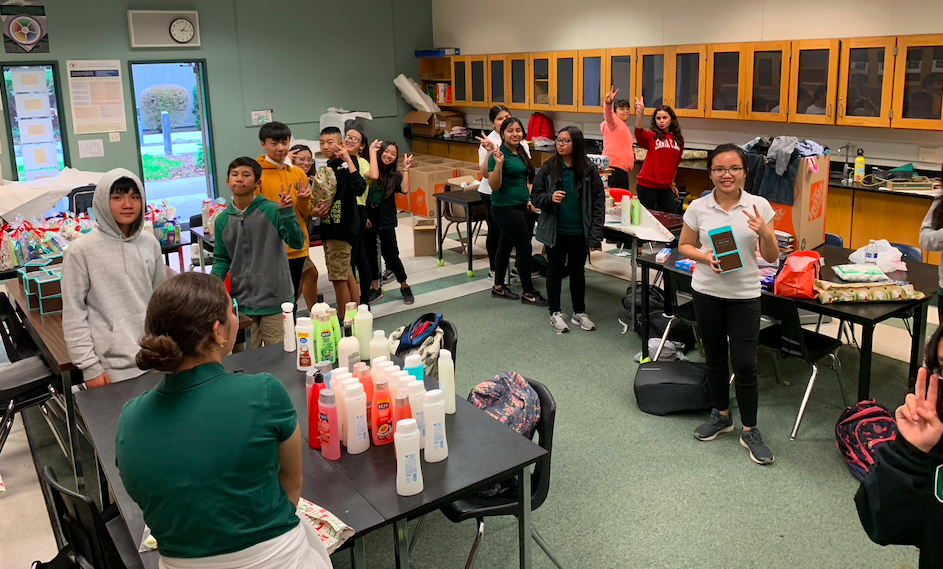 CCA students gathered around toiletry items and giving a peace sign.