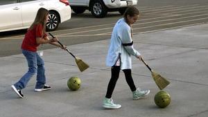 students pushing bowling balls with brooms