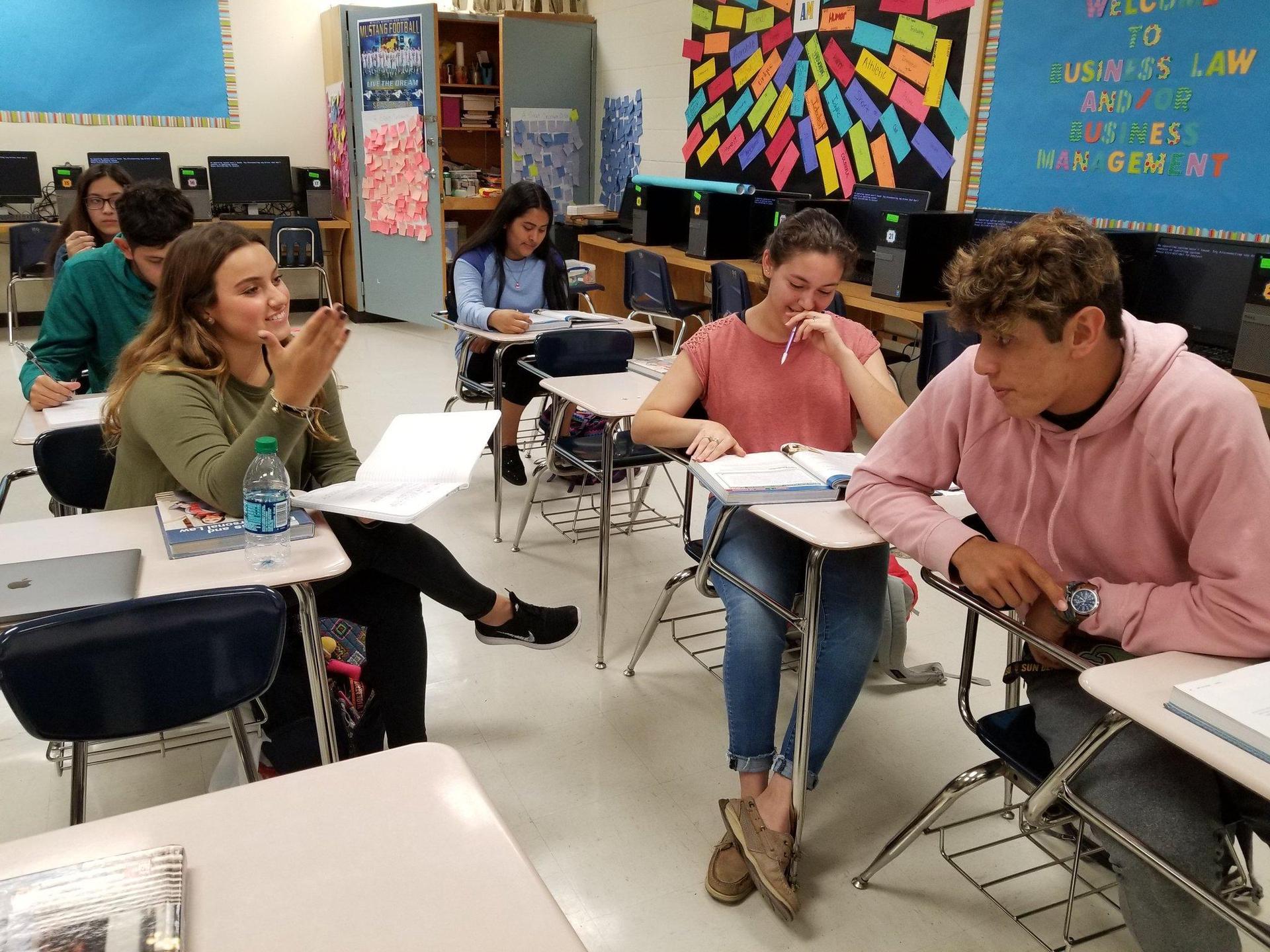 students sitting in desks conversing