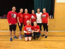 Teachers dressed in athletic gear holding a volleyball.