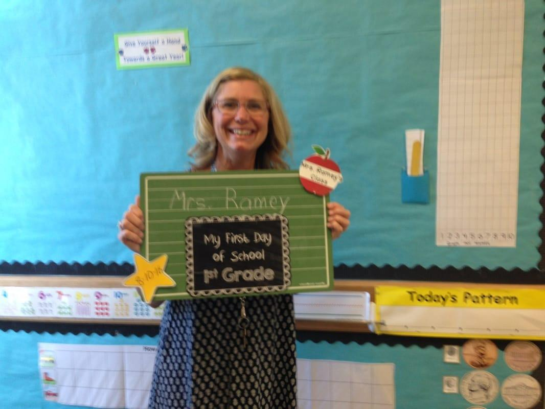 Ms. Ramey holding a first day of school sign