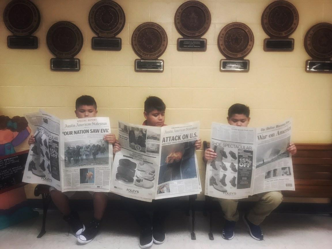 Students read newspapers dated Sept. 11, 2001.