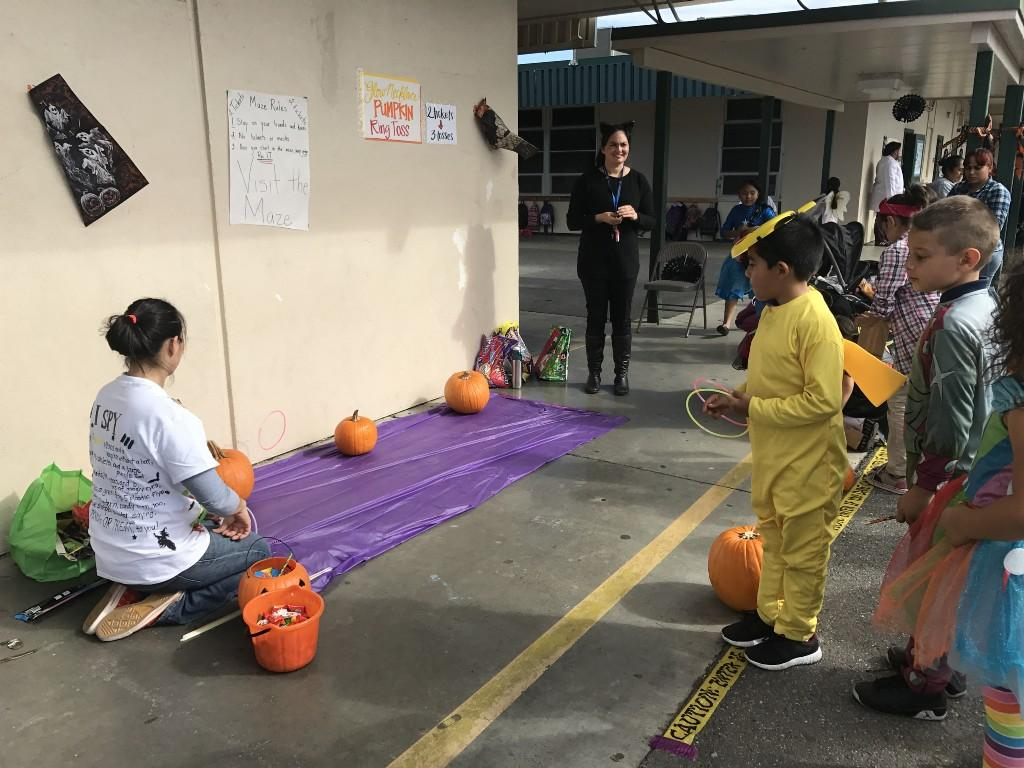 Kids participating in pumpkin ring toss