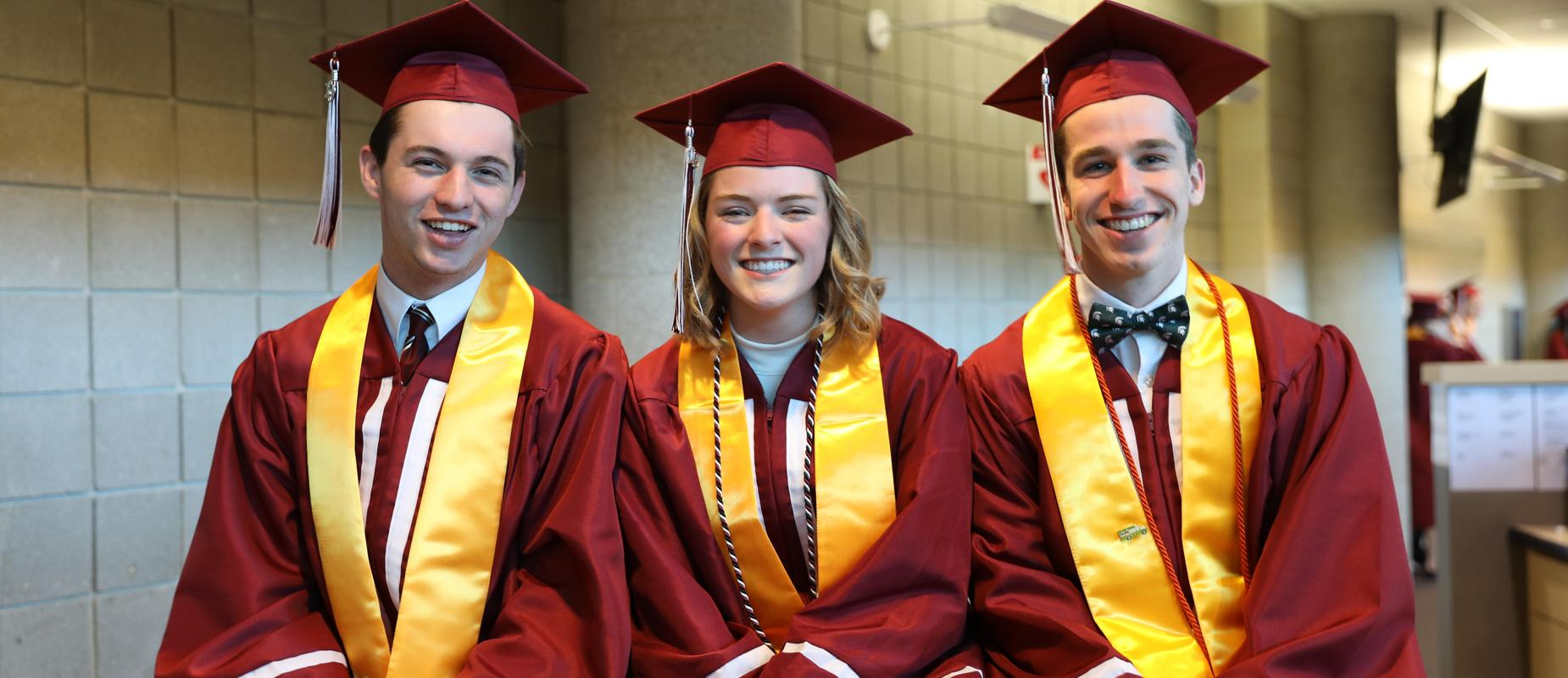3 grads in maroon robes and caps with yellow sashes