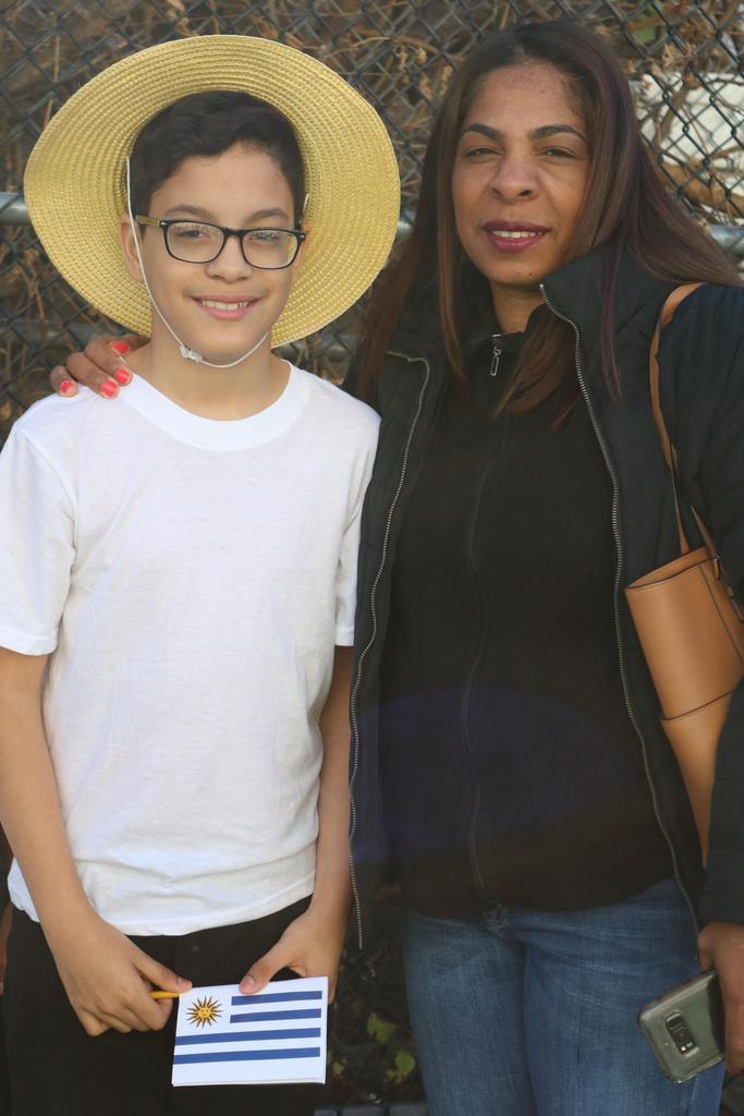 a proud mother with her son who wears glasses and has on a straw hat