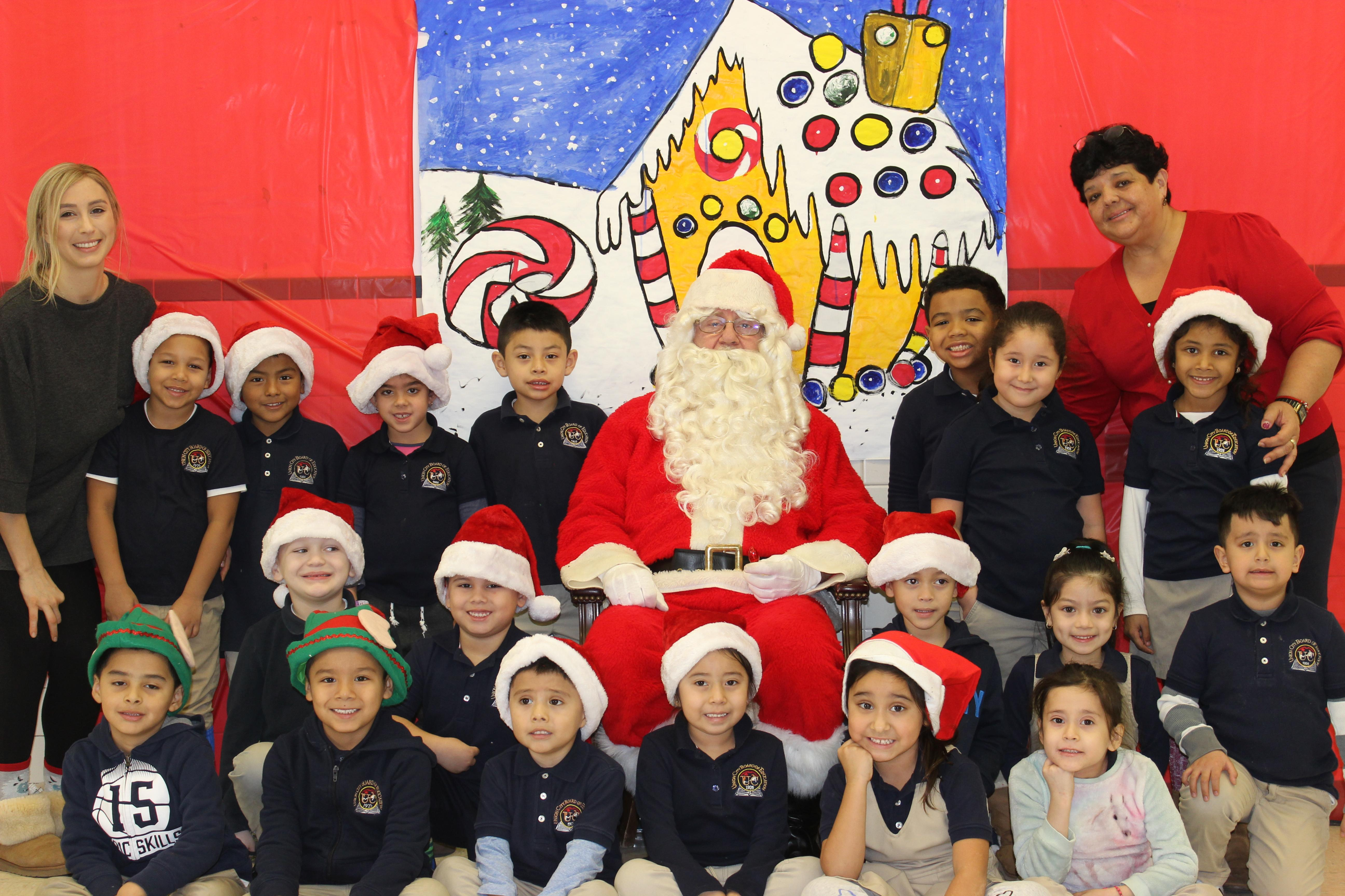 kindergaren class with teacher and aides posing with santa