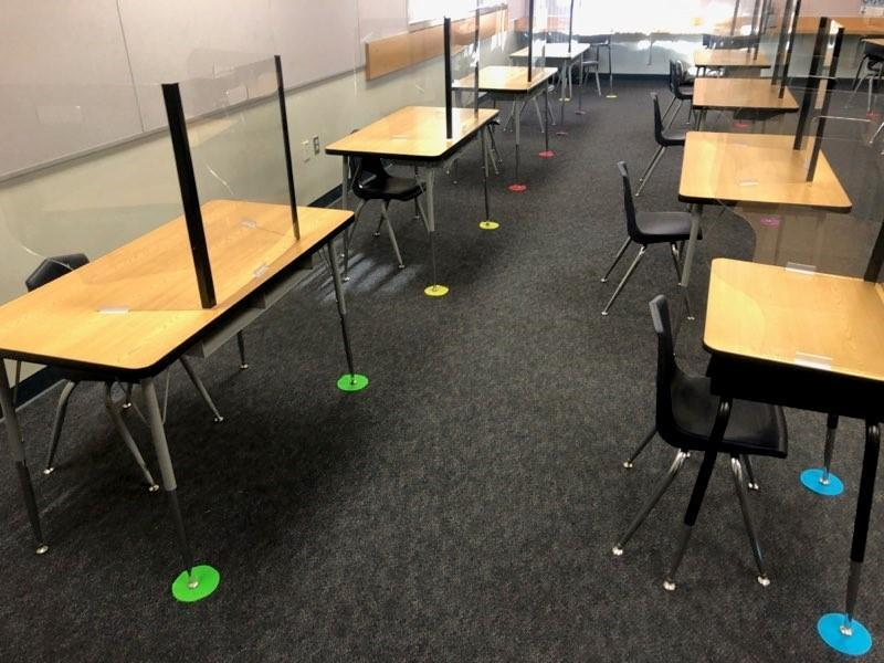 round dots on carpet to show proper desk placement for social distancing