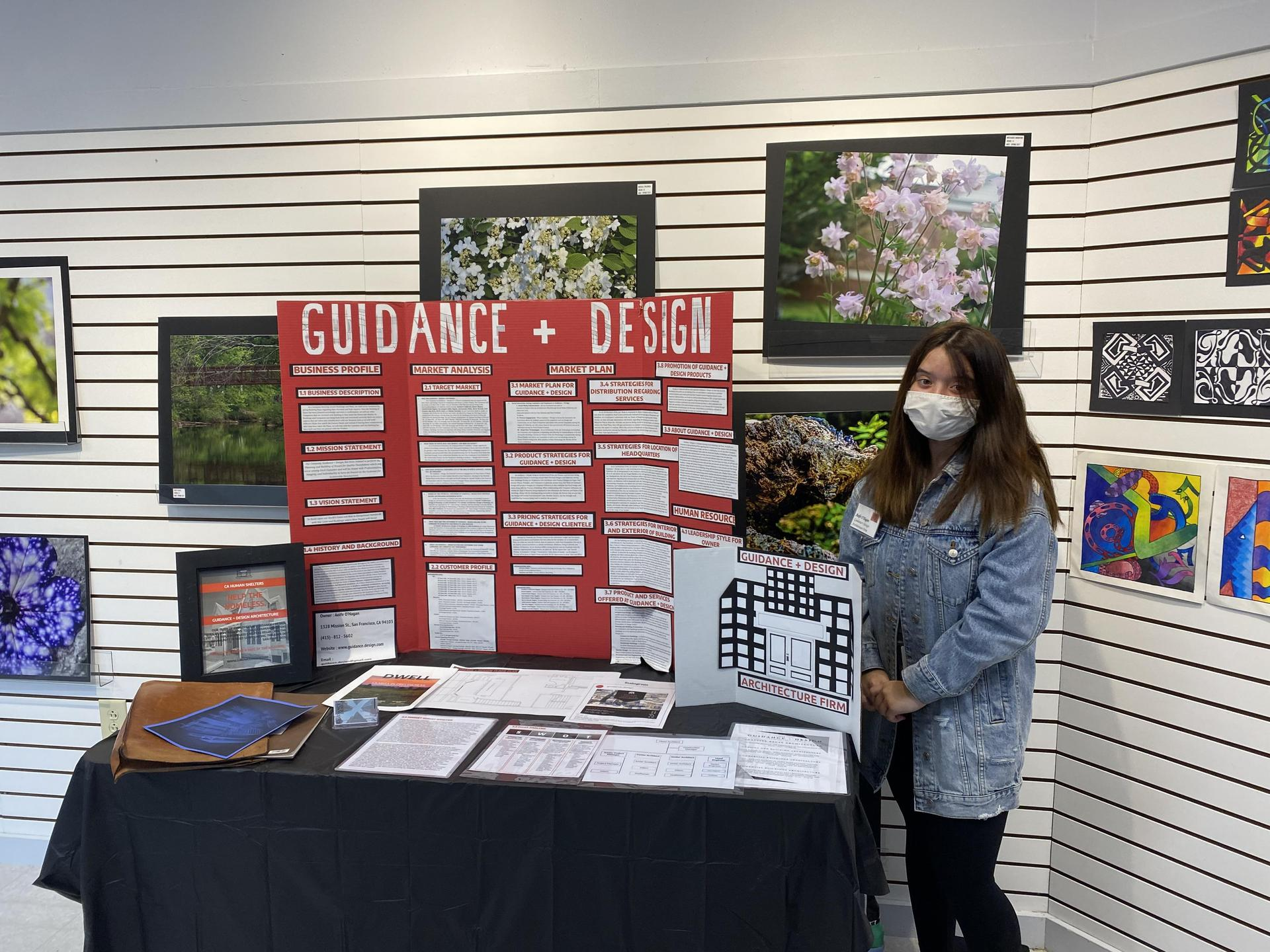 student in front of red presentation board