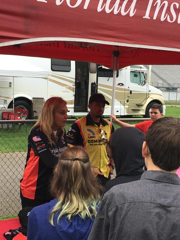 Racing team talks to kids at the track.
