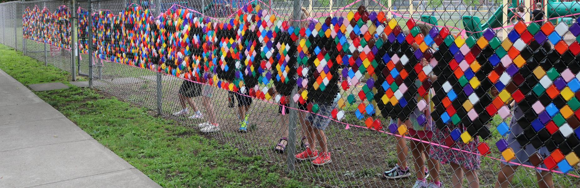 Photo of Lincoln playground mosaic, with students working on the other side (just their feet showing)