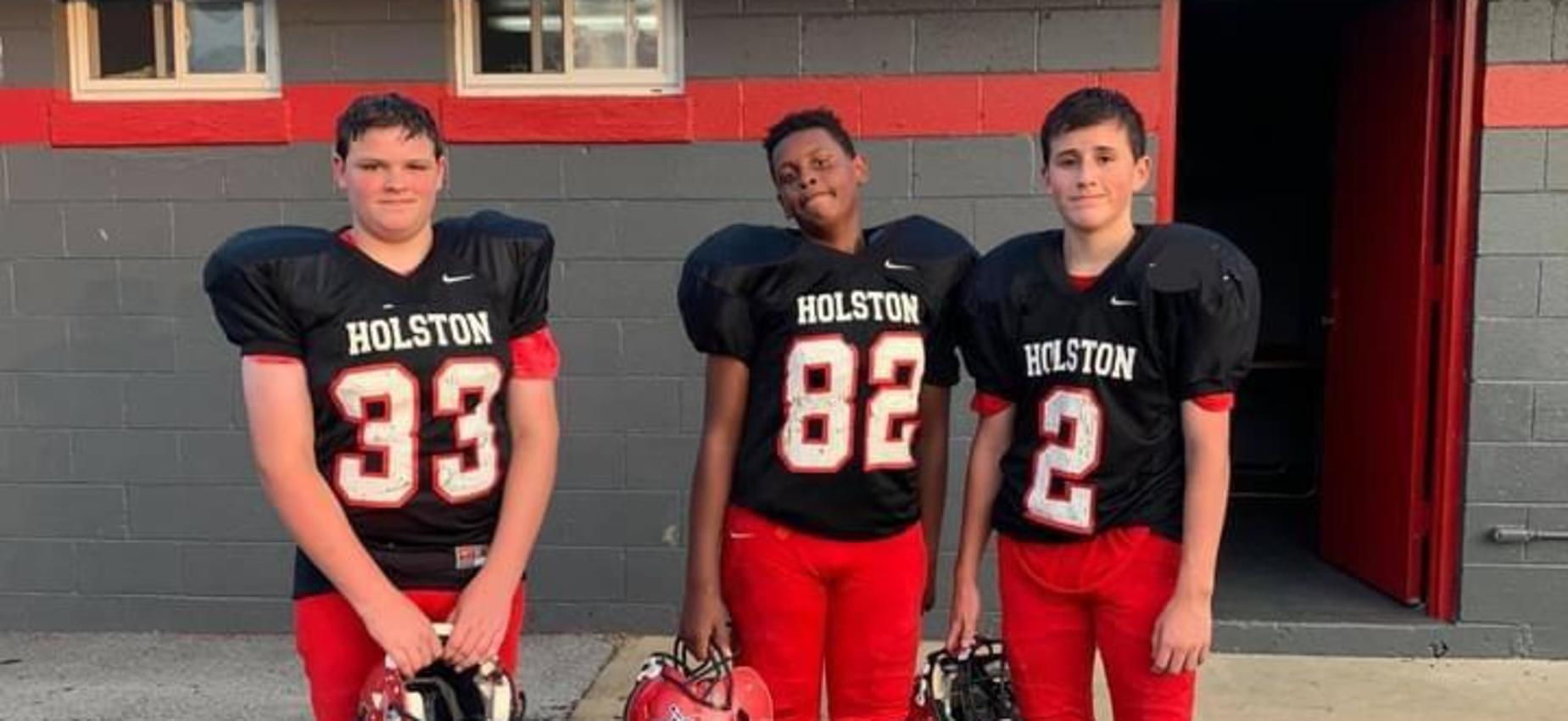 Football players pose outside a field house.