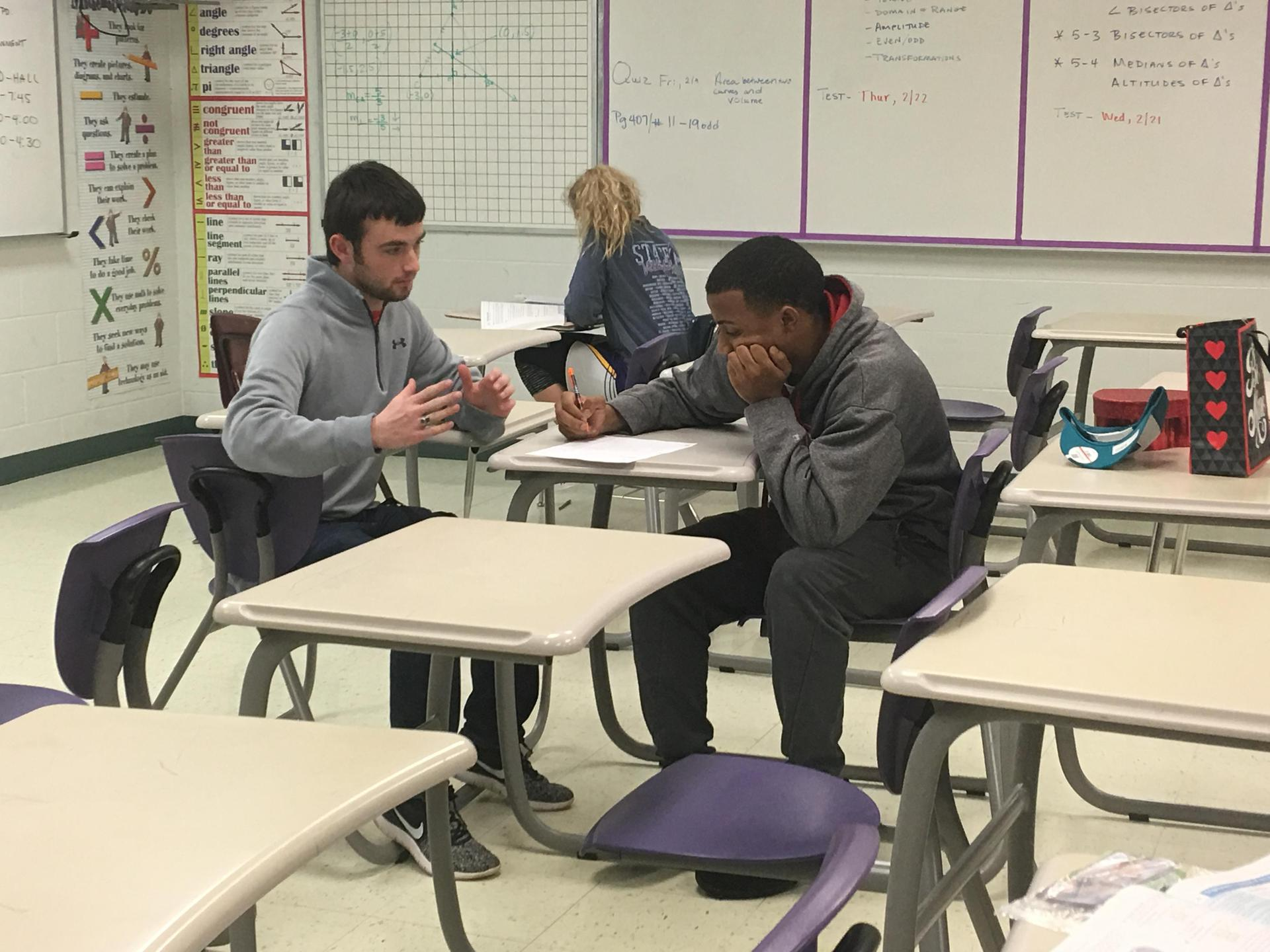two male students sitting in desks talking