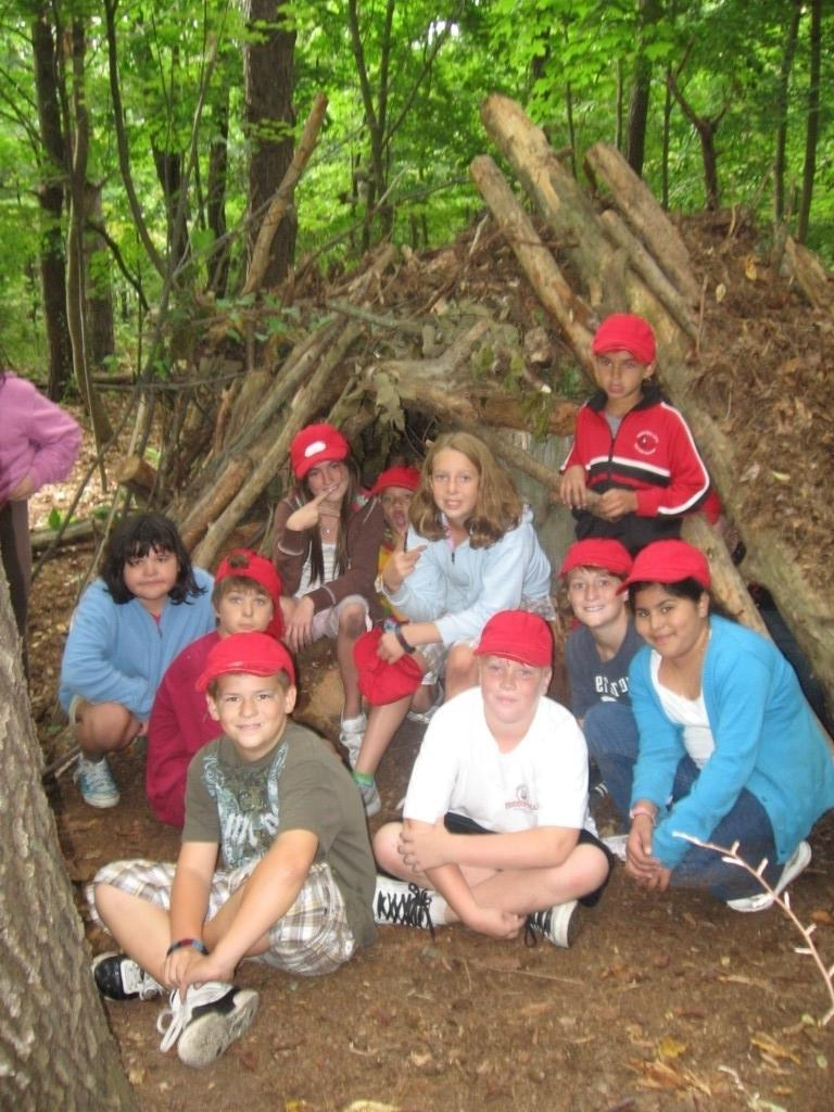 kids sit under tepee they built with sticks