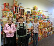 4 students standing in front of a large pile of cereal boxes