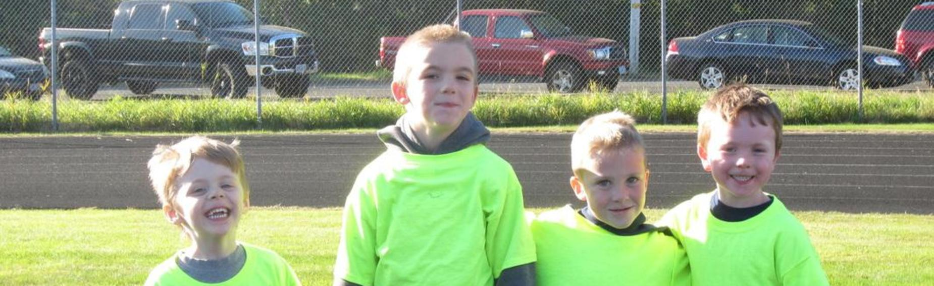 Four boys standing together smiling in florescent tee-shirts