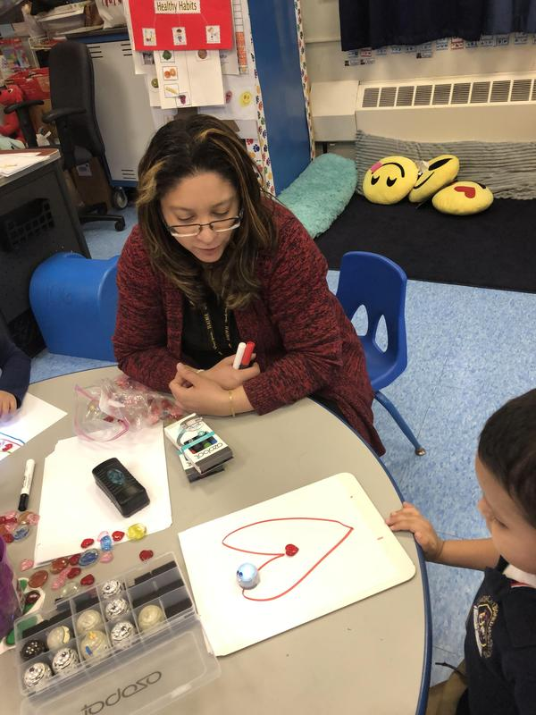 Ms. Ortiz with student who drew a heart and has ozobot coded to trace line