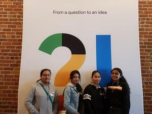 8th grade students posing in front of one of the Google Science Fair signs.