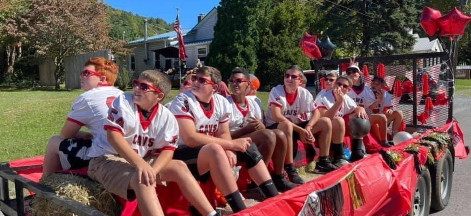 A group of football players rides on a float in a parade.