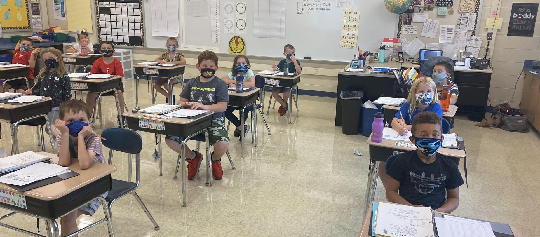 students sitting at desks with masks on