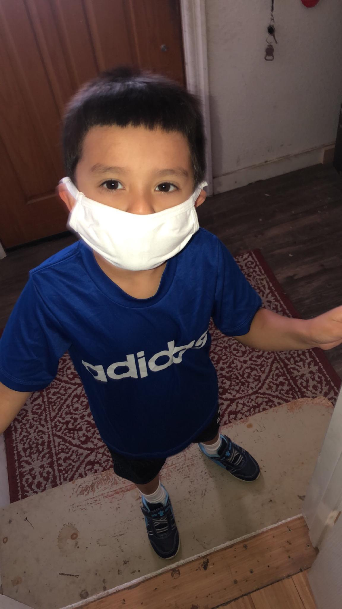 young boy wearing mask and posing for picture.