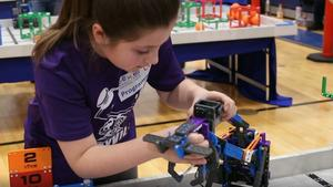 Scituate student repairing robot for competition