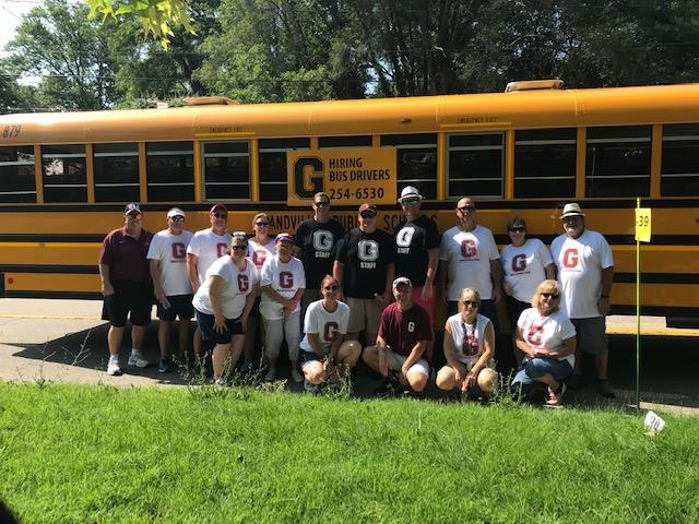 bus drivers stand in front of bus in white and black and maroon t-shirts