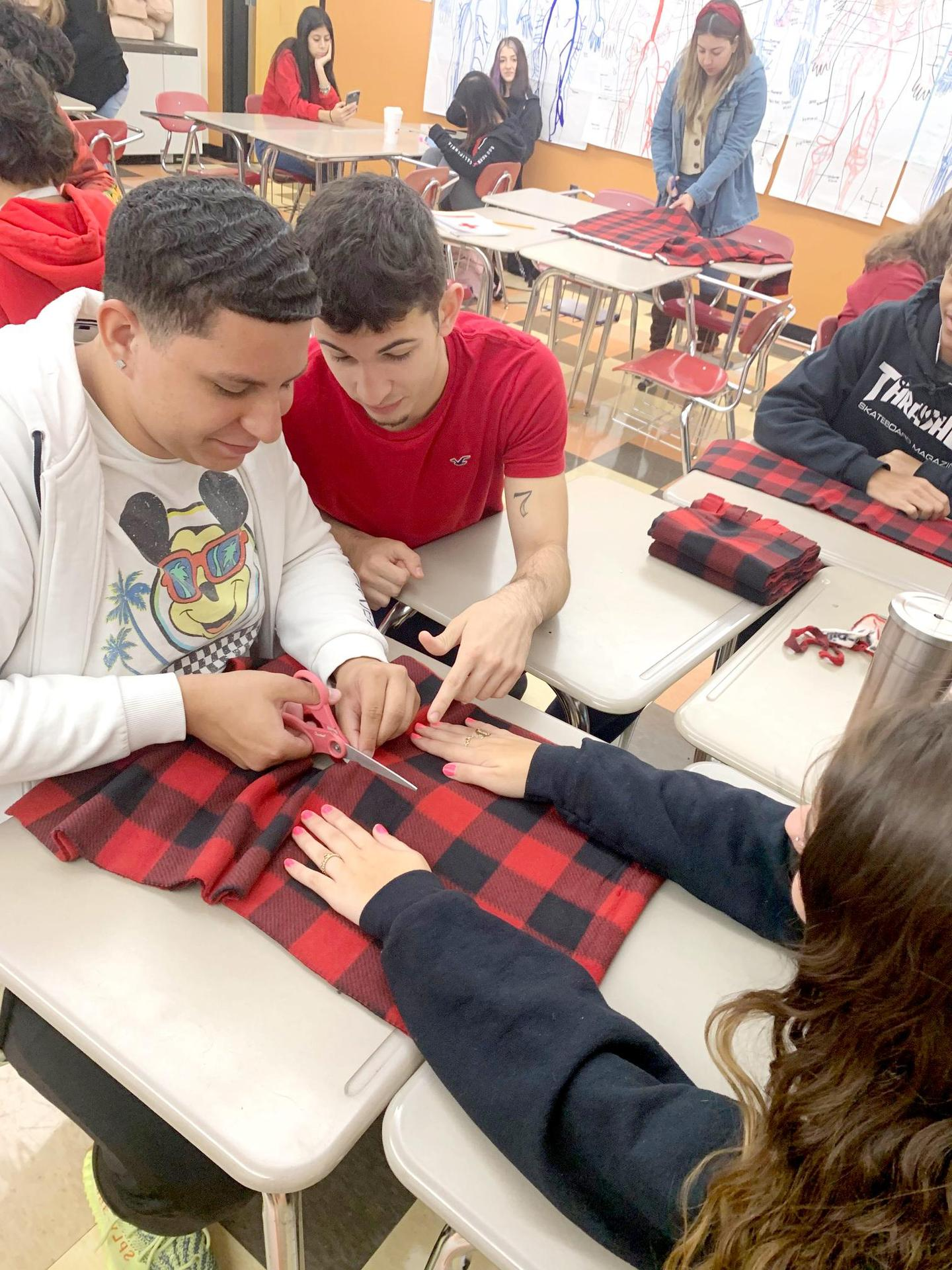 Two students hold a piece of fabric while a third cuts it