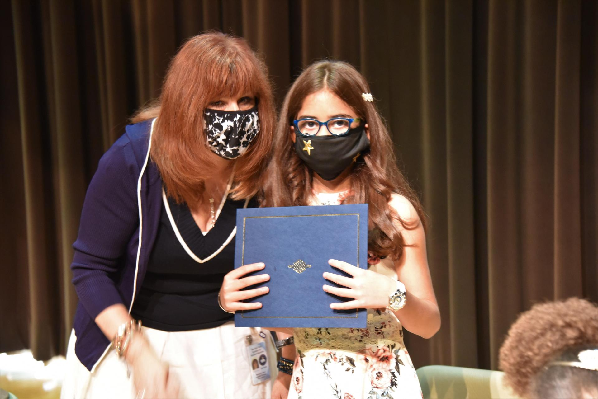 A teacher hands a diploma to a student as they both pose for a photograph