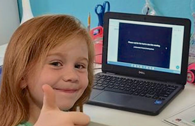 Young female student in front of a laptop looking at the camera giving a thumbs up