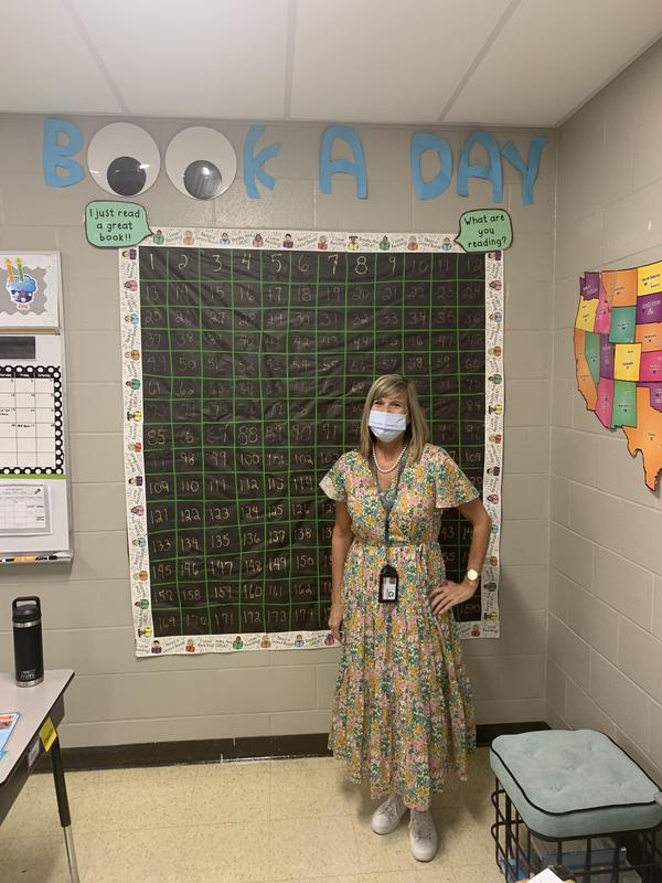 Elementary school teacher stands in front of classroom poster