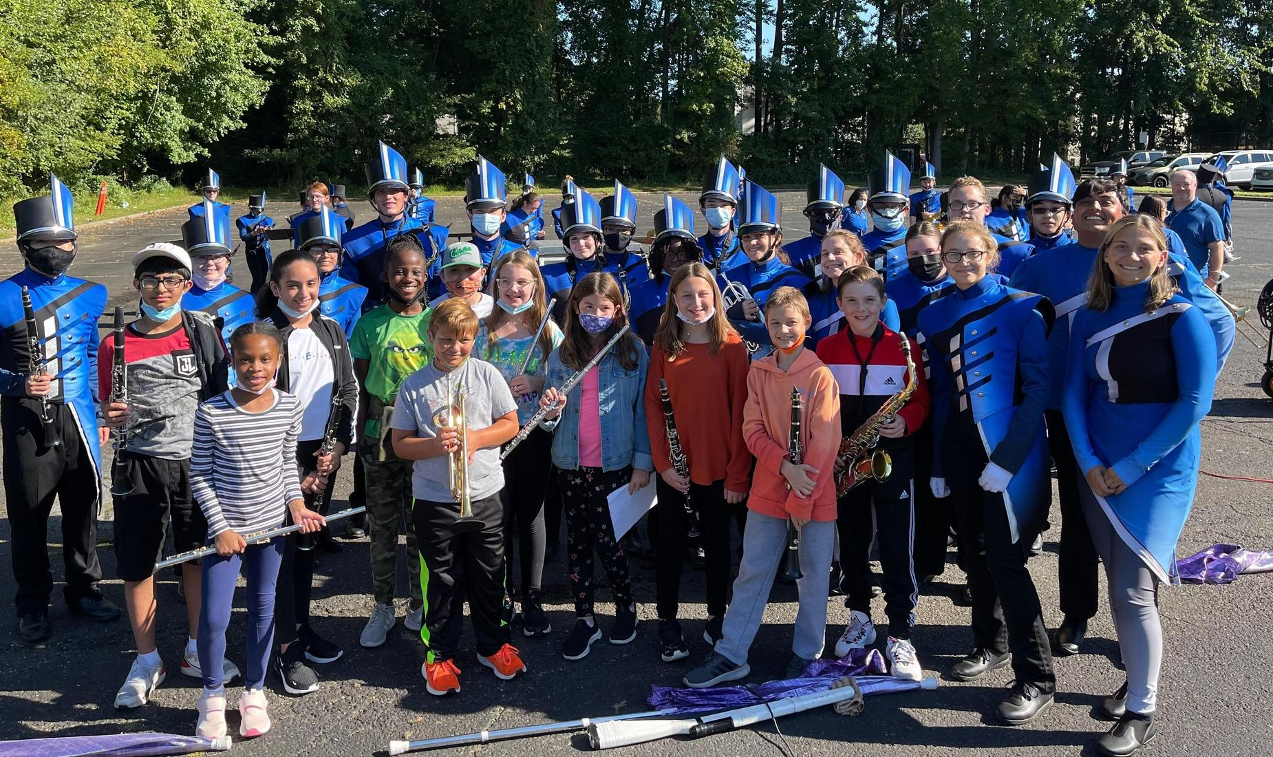 Members of the high school marching band in their band uniforms pose with members of the Struble elementary band.