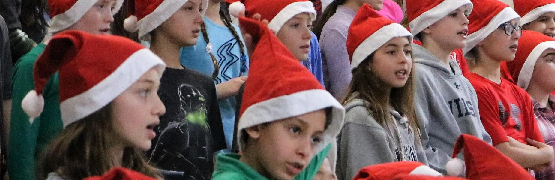 Photo of Wilson 5th graders wearing santa hats during holiday concert