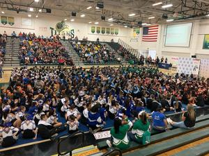 Various cheer teams sitting on the gym floor listening to Riverside County Superintendent of Schools giving a speech.