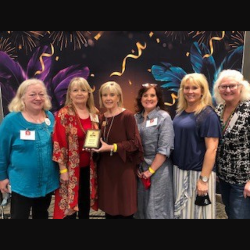 5 women surround one holding a plaque