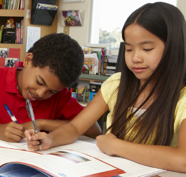 Two young students working on reading assignment.