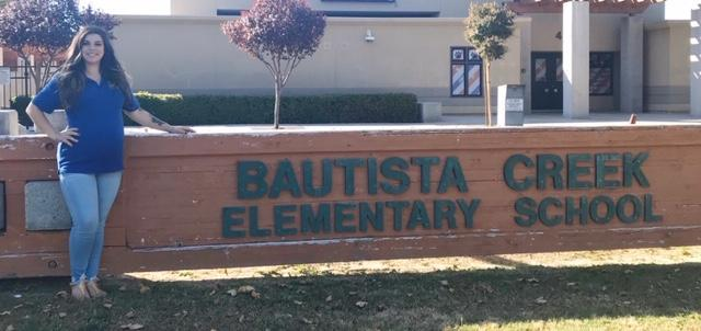 Jordyn Heier standing in front of a Bautista Creek sign