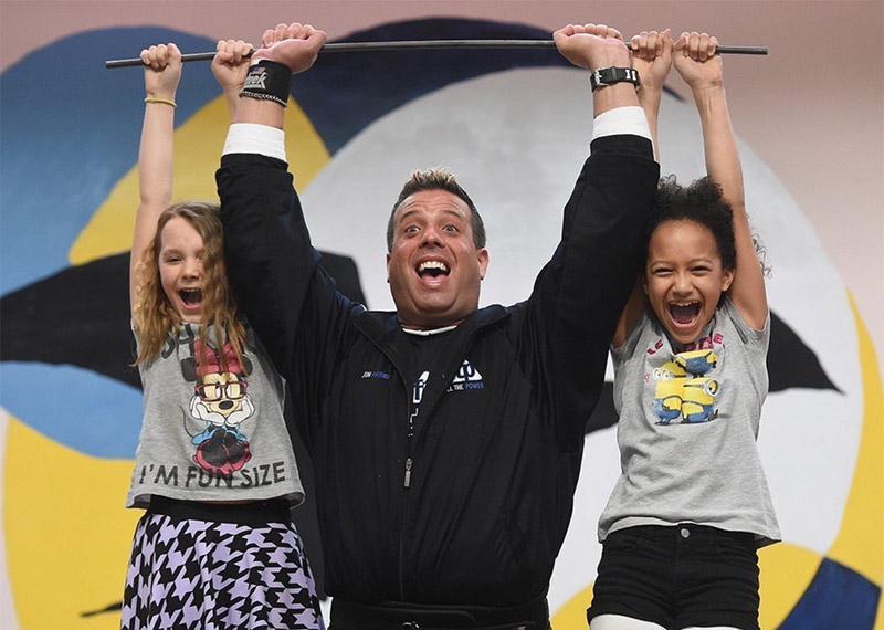 John Pritikin lifting two kids