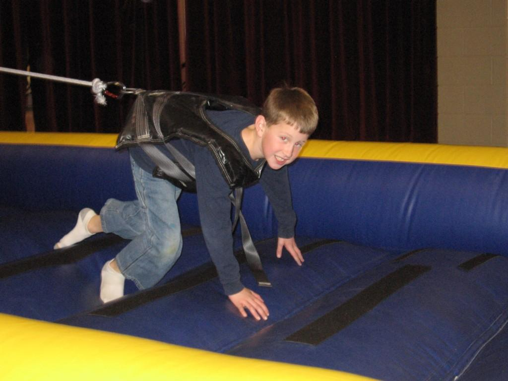 boy in harness on inflatable slide