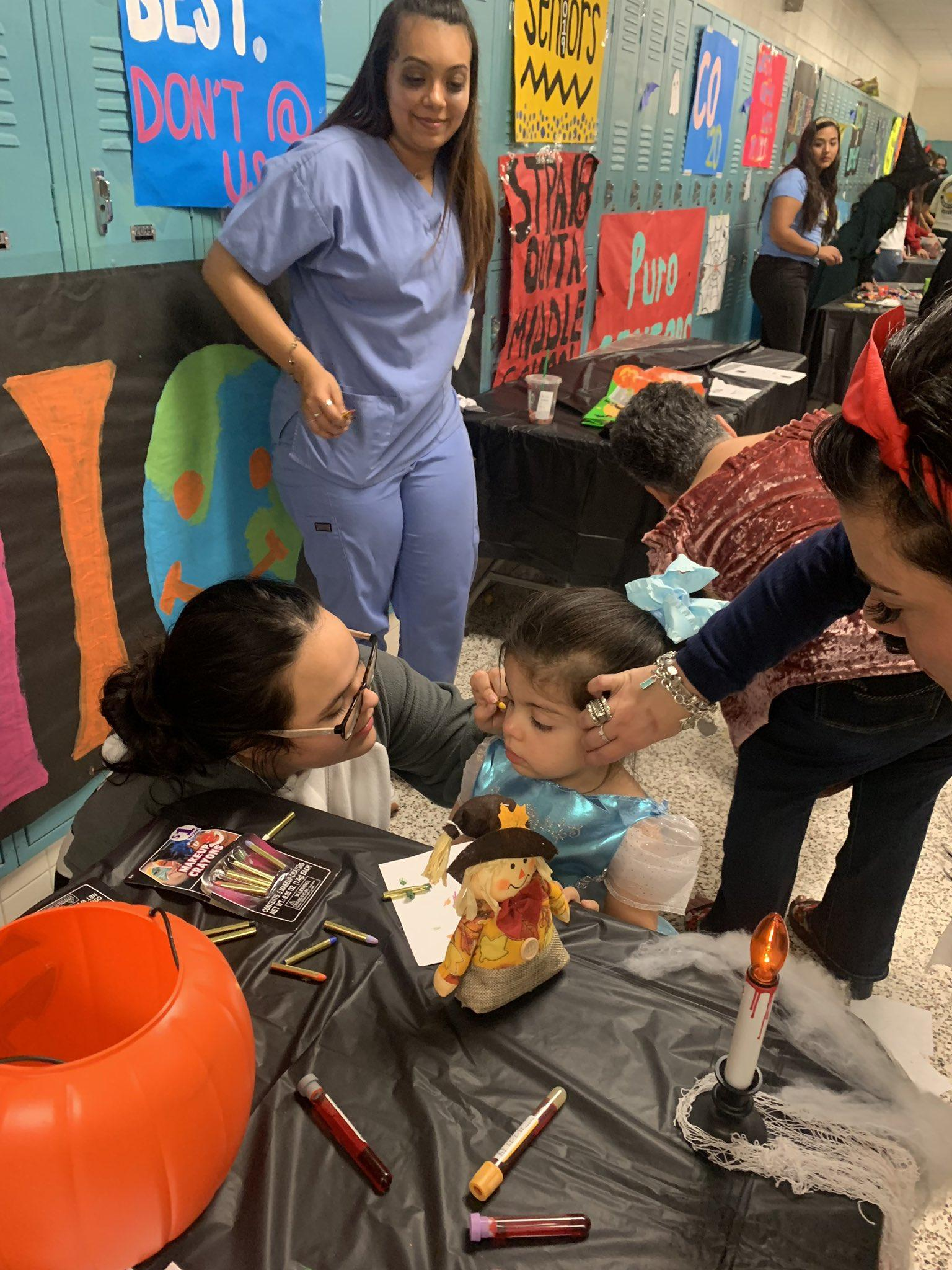 two women putting makeup on a child's face for Halloween