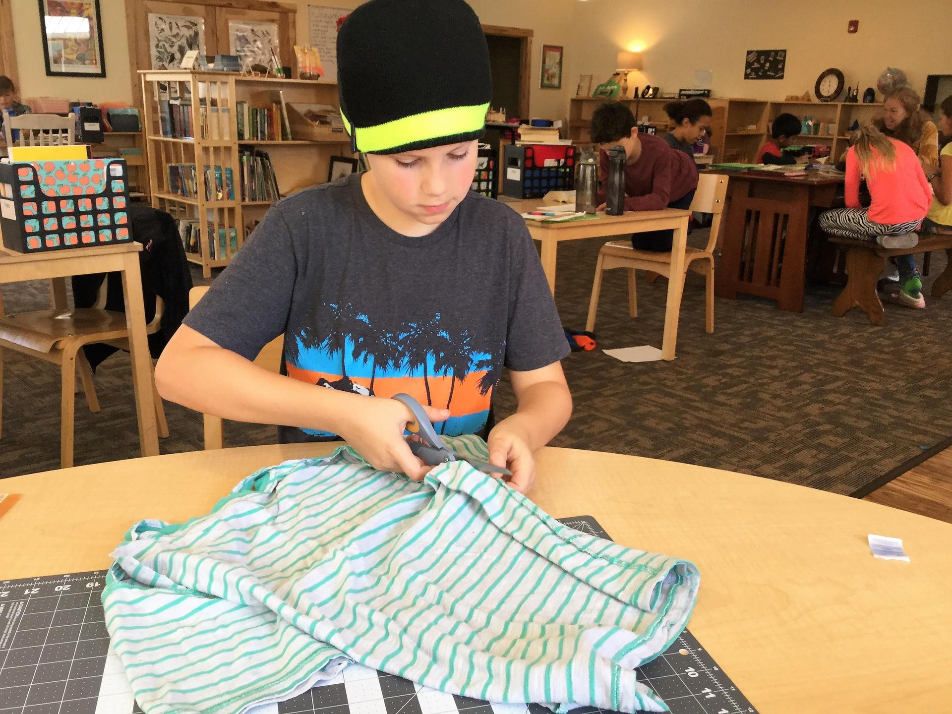 Student cutting fabric