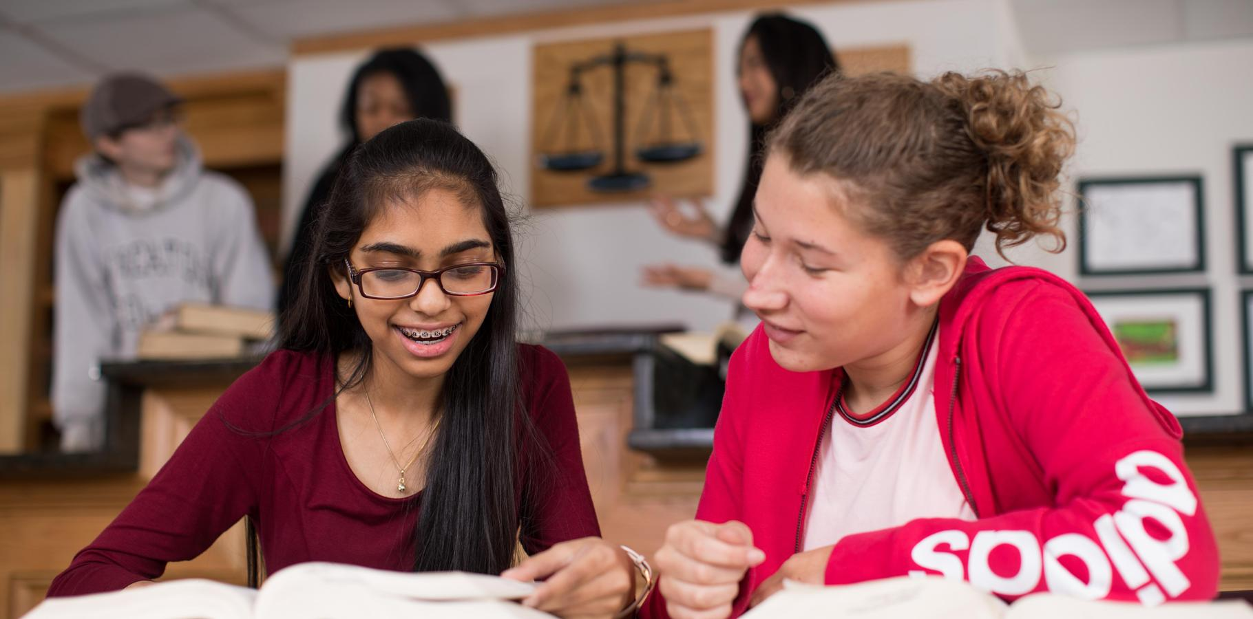 Two students smile while looking at a book in the HSC Courtroom