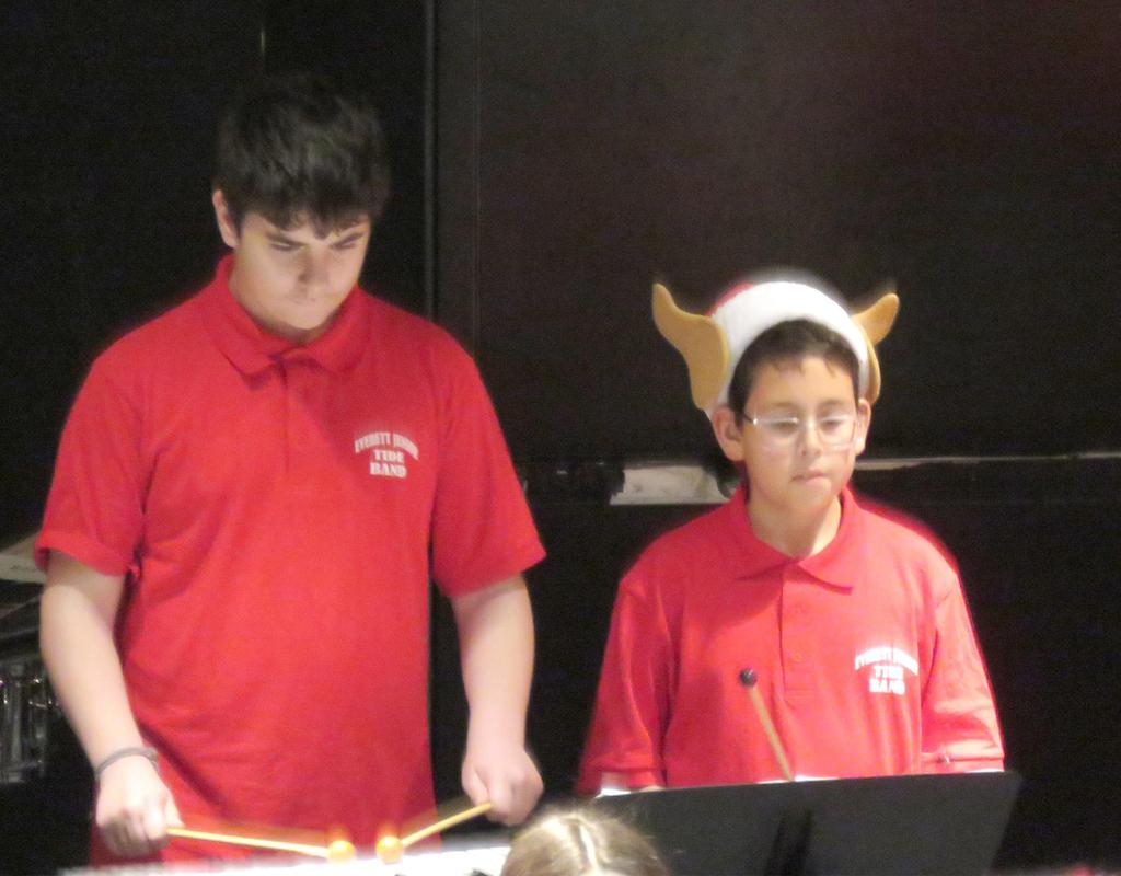 Two male drummers, one wearing a Santa hat with antlers