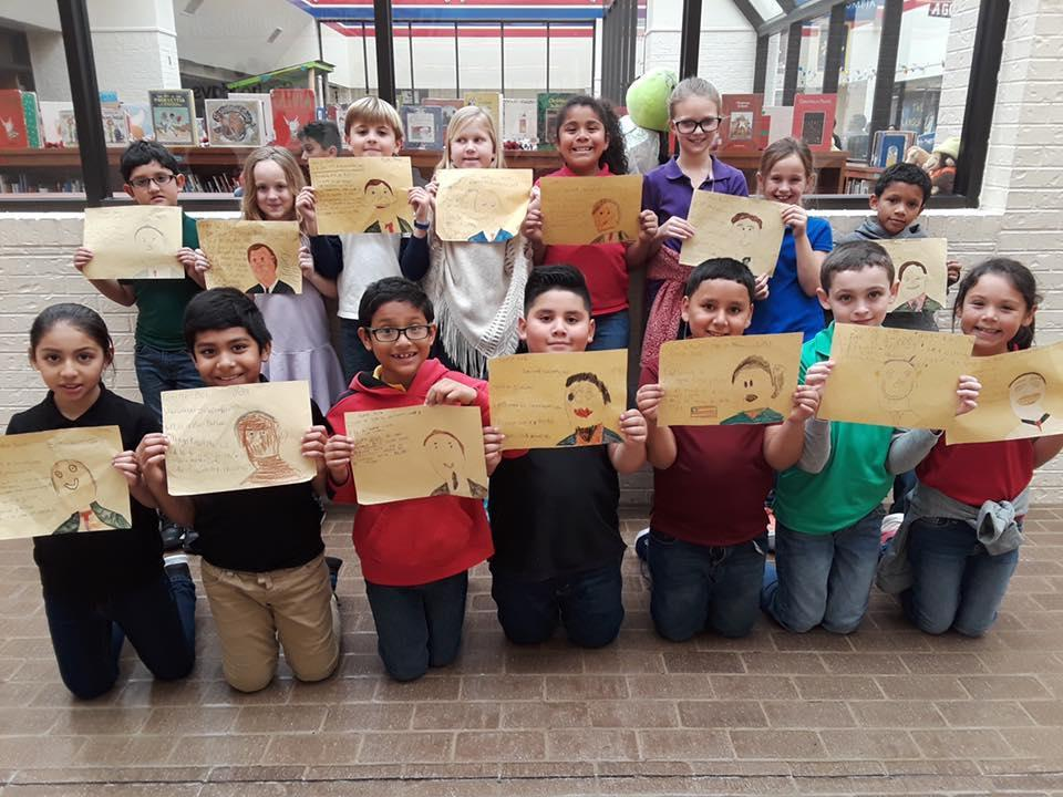 3rd grade students showing their artwork honoring the life of former President George W. Bush