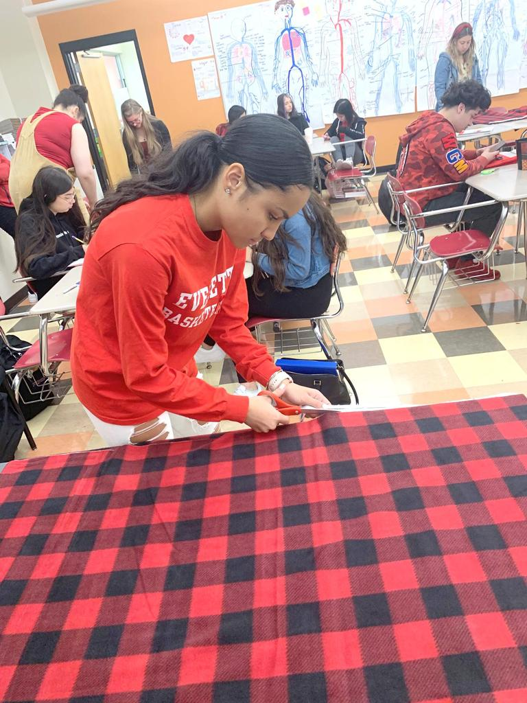 A student cuts a large piece of red plaid fabric