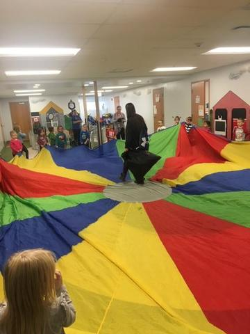 Pre-Kindergarten students participate in stretching out parachute for a team activity