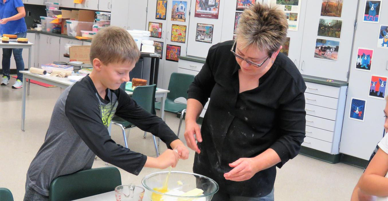 Lee art teacher Kathy Bailey watches carefully as a student cracks an egg into a cake mix.