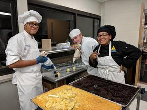 Three student chefs posing while creating desserts