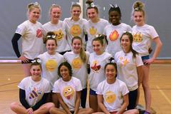 The Mead gymnastics team with emoji t-shirts on posing for a team picture.