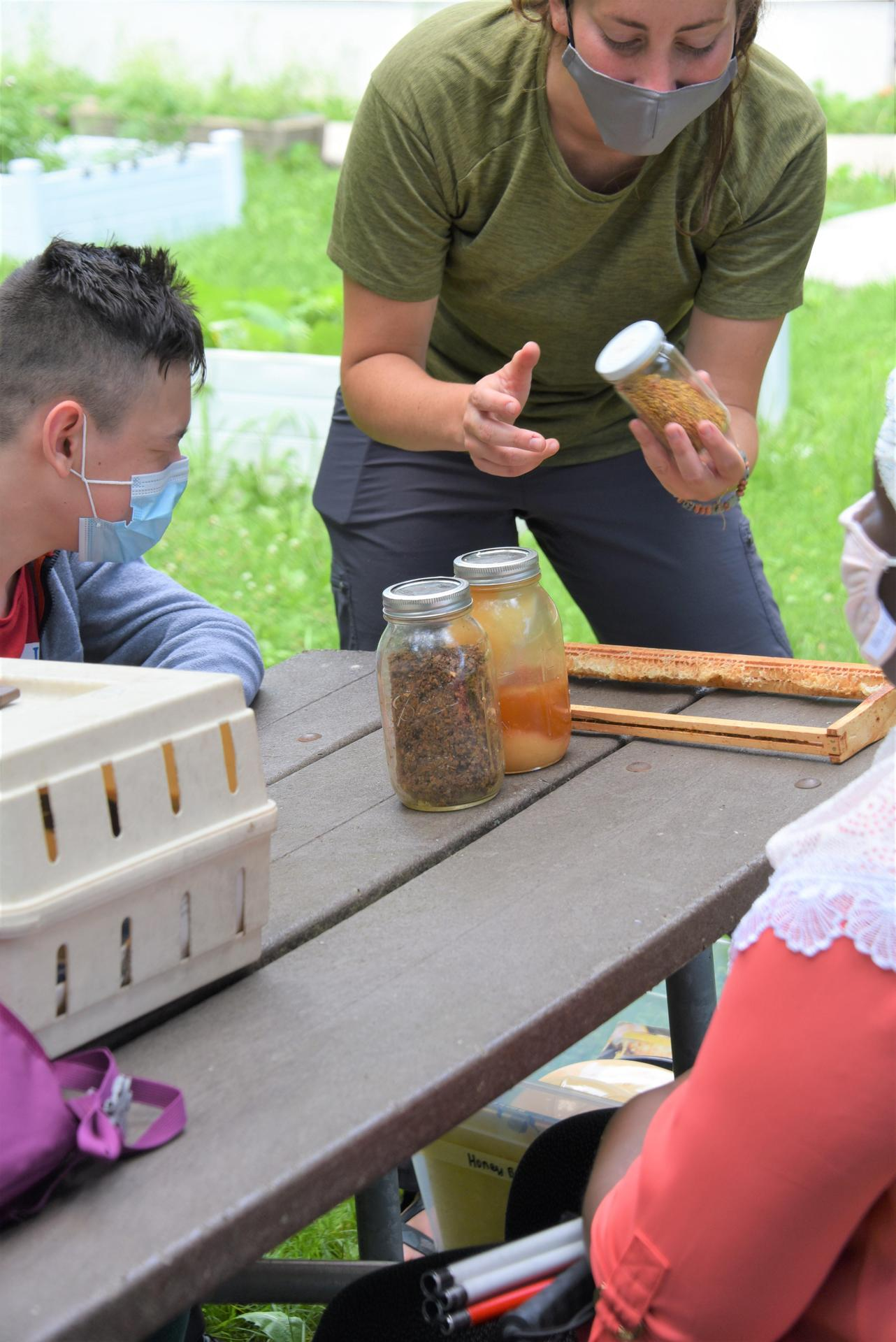 A woman stands in front of students at a picnic table holding a jar of pollen