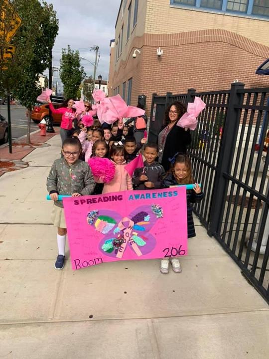 group of kids with a banner that says spreading awareness room 206 as other kids hold pink papers in their hands